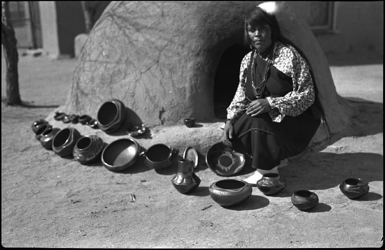 Rosalie Aguilar with carved and painted pottery. Photo by T. Harmon Parkhurst, Courtesy Palace of the Governors Photo Archives (NMHM/DCA), 004140.